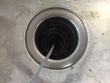 排水管のつまりを解除している写真