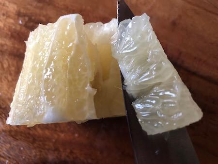 グレープフルーツ果実を包丁で切り出している写真