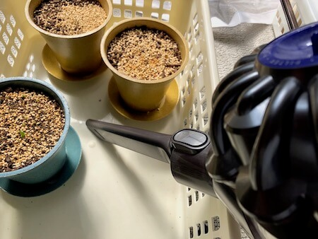 鉢の間を小型掃除機で清掃する写真