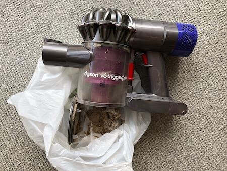 ゴミを捨てているダイソンの掃除機写真
