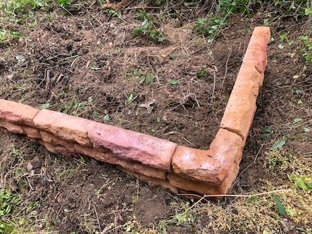 穴を掘りながら花壇ブロックを仮設置している写真