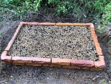 花壇の培養土に水を染み込ませている写真